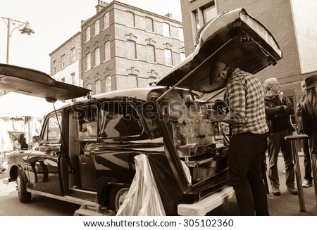 LONDON, ENGLAND, UK - MAY 4, 2014: Unidentified barista making coffee in mobile cafe (former old cab car) at Brick Lane market area. - stock photo