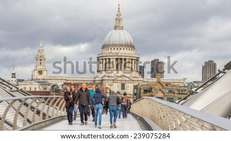 LONDON, ENGLAND, UK - OCTOBER 21, 2014: Tourists walking across the Milenium bridge to St. Paul Cathedral