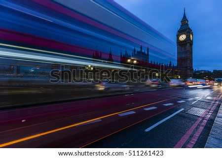 London, England, UK. Red buses blurred in motion on Westminster bridge with Big Ben, the Palace of Westminster in early morning before sunrise.
