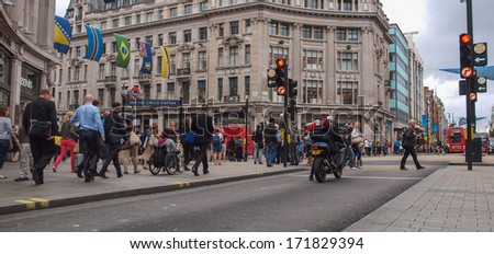 LONDON, ENGLAND, UK - SEPTEMBER 10, 2012: Oxford Street is one of the busiest high streets with tourist strolling in the winter shopping season - stock photo