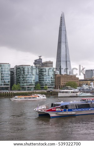 LONDON, ENGLAND, UNITED KINGDOM - MAY 07, 2014: Excursion boats sailing along the River Thames, with the Shard, and other modern glass-like buildings as background