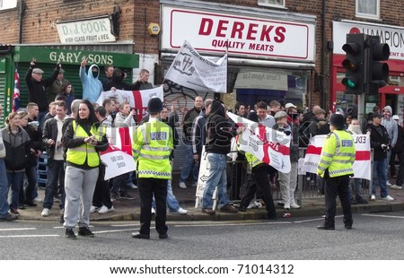 LONDON - FEB 12: English defence league protesters demonstrate behind police lines, against londons latest mosque being built at Dagenham, london, feb 12, 2011. - stock photo