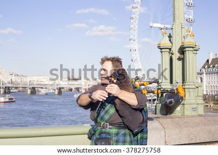 LONDON - FEB 16: Unidentified bagpiper on the Westminster Bridge on Feb 16, 2016 in London. In the UK the Great Highland bagpipe is commonly used in the military and often played in formal ceremonies - stock photo