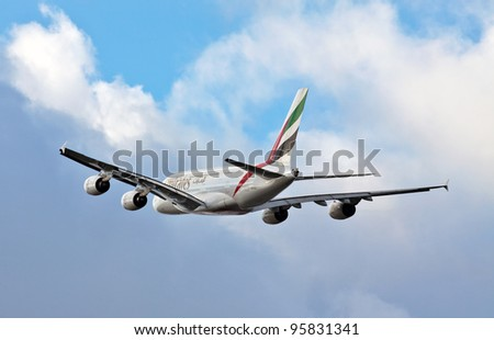 LONDON - FEBRUARY 19: An Emirates  Airbus A380 flys over the perimeter of Heathrow airport on February 19, 2012 in London. The A380 is the worlds largest jetliner seating up to 853 passengers - stock photo