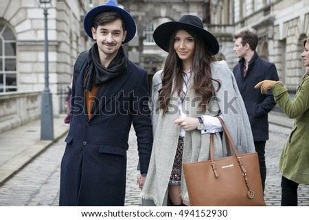 LONDON - FEBRUARY 18: Happy trendy couple  poses for photographers outside Somerset house during London Fashion week on February 18, 2014. Street fashion