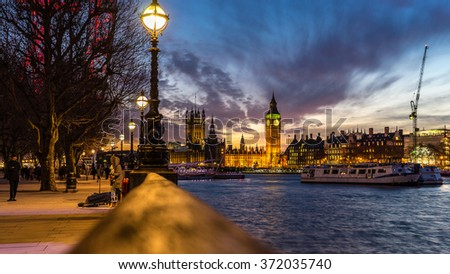 London, Great Britain - January 28, 2016: Musician playing in front of the Big Ben and Thames River at night - stock photo