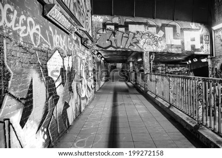 LONDON, GREAT BRITAIN - 18th of January 2014:Unknown artist painting graffiti and pedestrians on the Leake Street on 18th of January 2014 in LONDON, GREAT BRITAIN  - stock photo