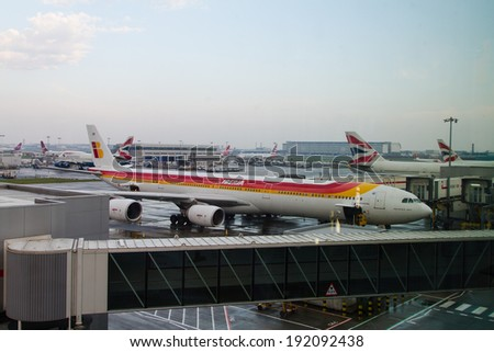 LONDON HEATHROW - APRIL 20: Spanish Iberia Airbus 340 parks at gate at Heathrow Airport in London on April 20, 2014. Heathrow had 65.7 million passengers arriving and departing in 2010. - stock photo