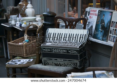 London - January 17, 2015. Flea market with old-fashioned goods displayed in London city, UK.  On 17 January 2015. Messy packed room full of antique objects like dolls, accordion, wicker  - stock photo
