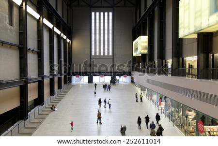 LONDON - JANUARY 18, 2015.People walking in the Turbine Hall in Tate Modern Art Gallery.It is located in the former Bankside Power Station, (a disused power station) in London, South Thames Embankment - stock photo
