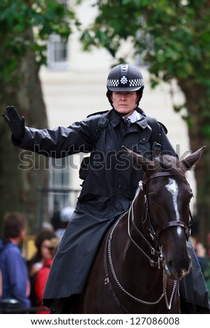 LONDON - JULY 4: A member of metropolitan police conducts traffic from the back of her horse on July 4, 2012 in London. Mounted police are employed increasingly in the UK for crime prevention. - stock photo