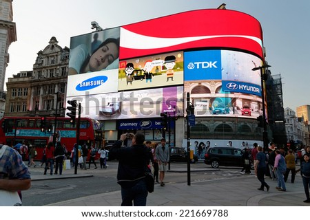 LONDON - JULY 1, 2014: Famous Piccadilly Circus neon signage shines at night. These signs have become a major attraction of London. - stock photo