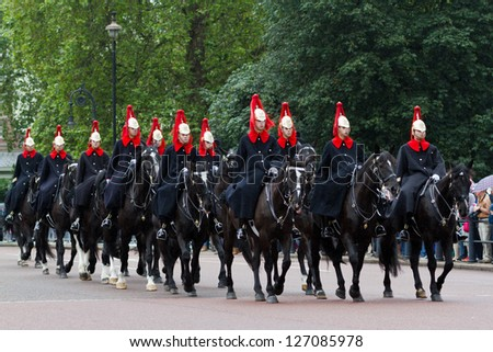 LONDON - JULY 4: Horse Guards arrive to Buckingham Palace during Changing the Guard ceremony on July 4, 2012 in London. Changing the Guard takes place at 11.30 am daily from May to July. - stock photo