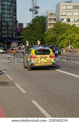 LONDON - JULY 1, 2014: London Metropolitan Police vehicle on Westminster Bridge. The Met was formed in 1829 and as of 2011 employed 48,661 staff making it one of biggest employers in London. - stock photo