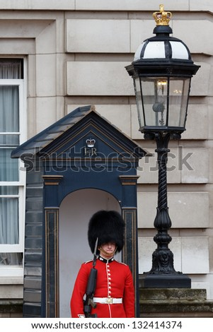 LONDON - JULY 4: Sentry of the Queen's Guard posted in front of Buckingham Palace on July 4, 2012 in London. Sentries are relieved during Changing of the Guard Ceremony.