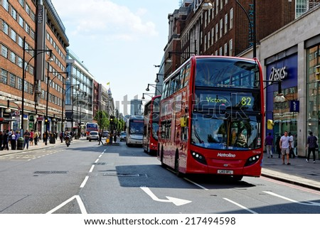 LONDON - JULY 1, 2014. Shoppers and bus services on Oxford street, the biggest shopping street in Europe, visited by millions of tourists. - stock photo