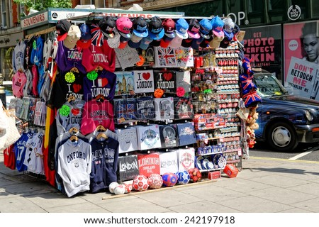 LONDON - JULY 1, 2014: Street vendor offers various colorful souvenirs at Oxford Street, where he competes with large supermarket chains.  - stock photo