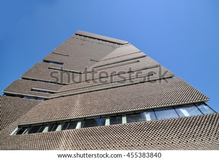 LONDON - JULY 19, 2016. The angular perforated brickwork of the Tate Modern art gallery extension designed by Herzog & de Meuron filters daylight in and emits artificial light, at Bankside, London.