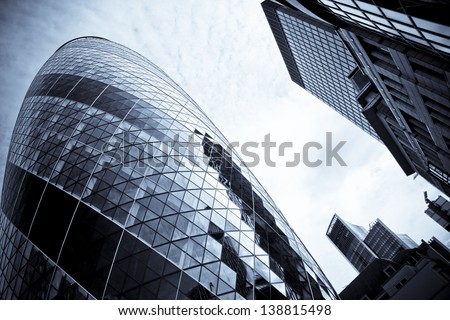 LONDON - JULY 28: The modern glass buildings of the Swiss Re Gherkin on July 28, 2007 in London, England. This tower is 180 meters tall and stands in the City of London Financial District. - stock photo