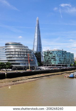LONDON - JULY 16. View along the south bank of the River Thames with the Shard skyscraper designed by Renzo Piano and City Hall by Foster and Partners on July 16, 2014 in central London, UK.