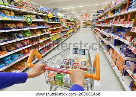 LONDON - JULY 3: View of a shopping trolley and aisle at a Sainsbury's supermarket on July 3, 2014 in London, UK. Sainsbury's is the UK's second largest supermarket with a revenue of £23 bln in 2013. - stock photo