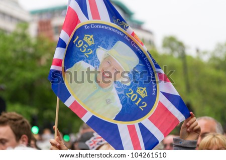 LONDON - JUNE 3: A commemorative flag is waved as crowds witness the Thames Diamond Jubilee Pageant on June 3, 2012 in London. - stock photo
