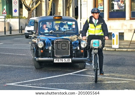 LONDON - JUNE 26 : A London Taxi or 'Black Cab' and a cyclist on June 26, 2014 in London, UK. All London cabs undergo a strict annual mechanical test before they are allowed to ply for hire.  - stock photo