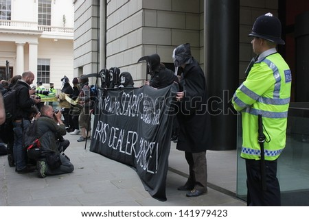 LONDON - June 12: A Police officer watches as demonstrators chant anti-arms slogans in Carlton Gardens on June 12, 2013 in London.