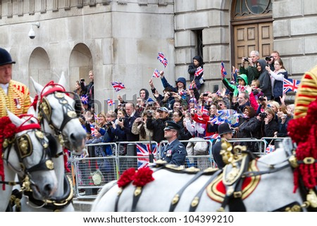 LONDON - JUNE 5: An unidentified crowd wave and smile when the Queen passes them during the carriage procession to Buckingham Palace during Diamond Jubilee celebrations on June 5, 2012 in London. - stock photo