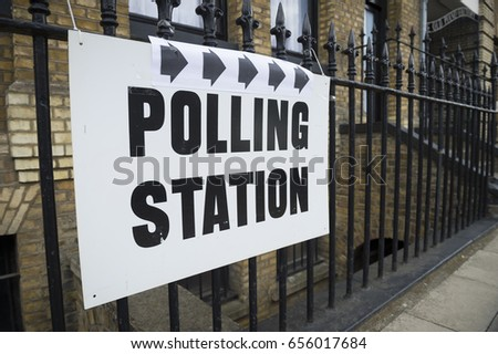 LONDON - JUNE 08, 2017: British election polling station sign hanging on classic wrought iron fence in front of yellow brick wall in London, UK