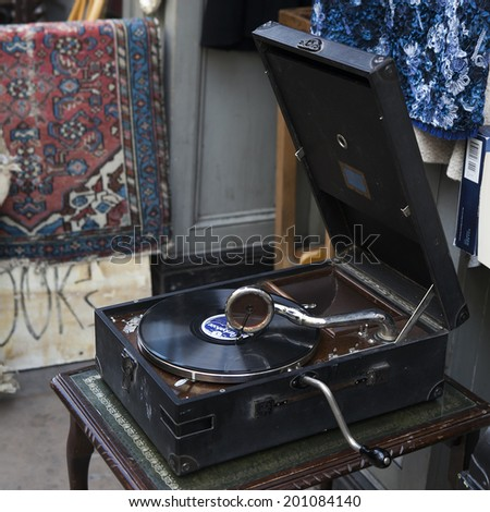 LONDON - JUNE 13, 2014. Flea market entrance with old-fashioned goods displayed in London city, UK, on 13 June 2014. window shop of old  shop with antique vintage pillow and lamp - stock photo