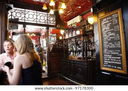 LONDON - JUNE 26: Interior of pub, for drinking and socializing, focal point of the community, on June 26, 2011, London, UK. Pub business, now about 53,500 pubs in UK, has been declining every year - stock photo