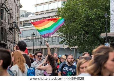 LONDON, JUNE 25, 2016: LGBT Gay Pride Parade, Crowd Of People With Man Waving Rainbow Flag. - stock photo
