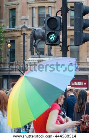 LONDON, JUNE 25, 2016: LGBT Gay Pride Parade. Gay symbol pedestrian crossing and woman with rainbow unbrella - stock photo