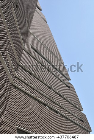 LONDON - JUNE 6, 2016. The angular perforated brickwork of the Tate Modern art gallery extension designed by Herzog & de Meuron filters daylight in and emits artificial light at Bankside, London.