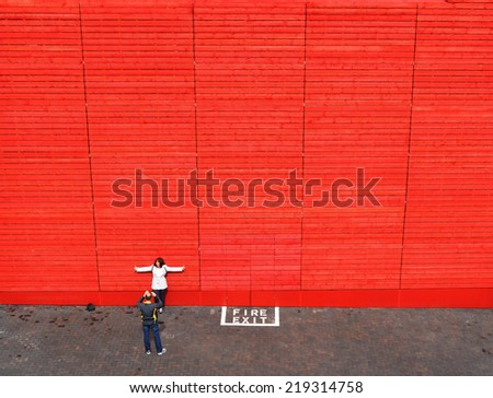 LONDON - JUNE 15. The red timber wall of the National Theatre's temporary venue is a popular backdrop for tourist photography on June 15, 2013, located at the South Bank, London, UK. - stock photo