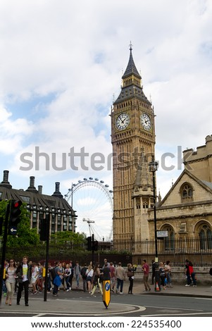 LONDON, JUNE 24 2014: Tourists walk with  BIG BEN and LONDON EYE on back ground in London. - stock photo