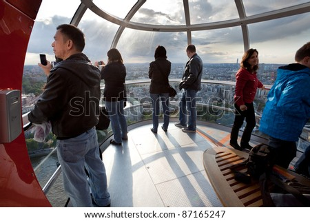 LONDON - JUNE 10: Unidentified tourists in London eye cabin observe the city from a bird's eye view on June 10, 2011 in London, UK. It's tallest Ferris wheel in Europe 135m (443ft) and most popular paid tourist attraction in UK - stock photo