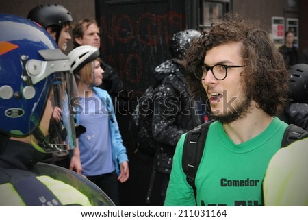 London - MAR 26: An unidentified protester talks to police while kettled behind police lines at a large anti cuts rally on Mar 26, 2011 in London, UK. An estimated 250,000 protesters joined the rally. - stock photo