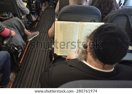LONDON - MAR 20 2015: Orthodox Jewish men pray on a airplane during flight.Jewish men are obligated to pray three times a day within specific time ranges - stock photo