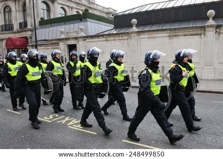 LONDON - MAR 26: Riot police deploy on a city centre street after violent riots break out during a 250,000 strong TUC organised anti public sector spending cuts rally on Mar 26, 2011 in London, UK. - stock photo