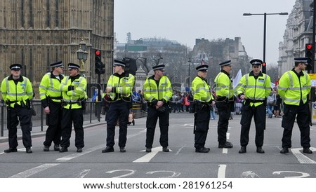 LONDON - MAR 26: Riot police stand guard at Westminster Palace road block as violent riots break out in the city centre during anti austerity rally on Mar 26, 2011 in London, UK. - stock photo