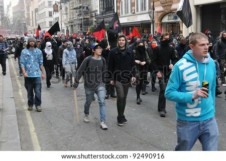 LONDON - MARCH 26: A breakaway group of protesters march through the streets of the British capital during a large austerity rally on 26 March 2011 in London, UK. - stock photo