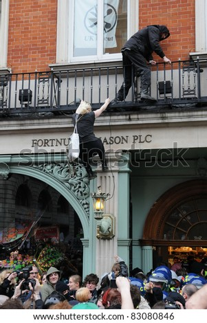 LONDON - MARCH 26: A breakaway group of protesters scale and occupy luxury department store Fortnum and Mason on Piccadilly during a large anti-cuts rally on March 26, 2011 in London, UK. - stock photo
