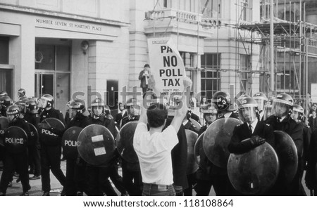 LONDON - MARCH 31: A protestor holds up a poster in front of riot police during the Poll Tax Riots on March 31, 1990 in London. The demonstration was against the unpopular Community Charge. - stock photo