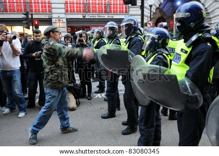 LONDON - MARCH 26: An unidentified protester confronts riot police during a large anti-cuts rally March 26, 2011 in London, UK. - stock photo