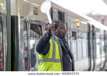 LONDON - MARCH 31, 2016: London Bridge Station, Train Conductor Signals Departure - stock photo