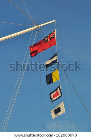 LONDON - MARCH 8. Maritime flags flying on the Cutty Sark on March 8, 2014, the most famous tea clipper built in 1869, showing the Red Ensign and J K W and S nautical flags, at Greenwich, London. - stock photo