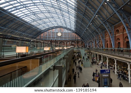 LONDON - MARCH 8: People rushing to trains in St Pancras station, home of the Eurostar train, a very modern and one of the most beautiful train stations of London. London, UK, March 8, 2013. - stock photo