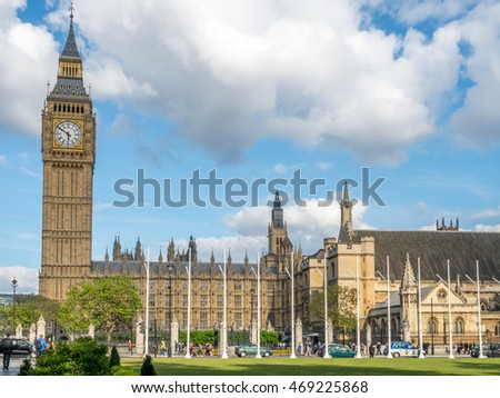LONDON - MAY 24: Big Ben clock tower and Palace of Westminster view from Parliament square garden under cloudy blue sky in London, England, on May 24, 2016.